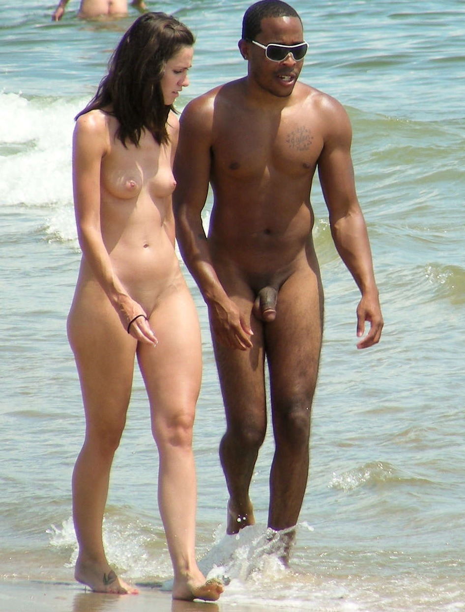Couple walking together at the nude beach.