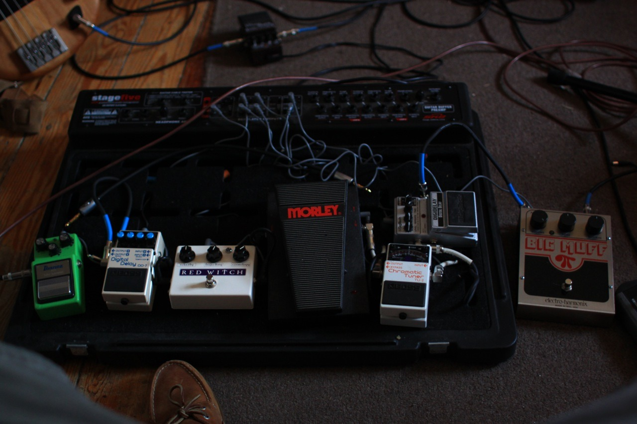 the pedalboard as it sits in it's glory. from right to left: big muff pi, digitech digital delay, boss tu2, morley bad horsie, red witch moon phaser, boss dd7, and that iconic, slime-green glory box on the end, the custom tube screamer ts9. -np