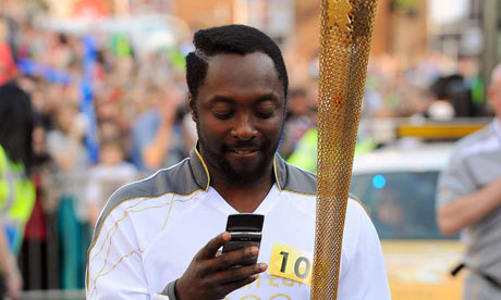 Will.I.Am texting while he bears the Olympic torch.