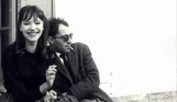 "vlorin:  THIS IS THE STORY OF HOW ANNA KARINA & JEAN-LUC GODARD FIRST ""GOT TOGETHER""  Anna Karina: That happened while we were shooting the picture in Geneva. It was a strange love story from the beginning. I could see Jean-Luc was looking at me all the time, and I was looking at him too, all day long.  We were like animals. One night we were at this dinner in Lausanne. My boyfriend, who was a painter, was there too. And suddenly I felt something under the table – it was Jean-Luc's hand. He gave me a piece of paper and then left to drive back to Geneva. I went into another room to see what he'd written.  It said, ""I love you.  Rendezvous at midnight at the Café de la Prez."" And then my boyfriend came into the room and demanded to see the piece of paper, and he took my arm and grabbed it and read it.  He said, ""You're not going."" And I said, ""I am."" And he said, ""But you can't do this to me.""  I said, ""But I'm in love too, so I'm going."" But he still didn't believe me. We drove back to Geneva and I started to pack my tiny suitcase.  He said, ""Tell me you're not going."" And I said, ""I've been in love with him since I saw him the second time. And I can't do anything about it."" It was like something electric. I walked there, and I remember my painter was running after me crying. I was, like, hypnotized – it never happened again to me in my life.  So I get to the Cafe de la Prez, and Jean-Luc was sitting there reading a paper, but I don't think he was really reading it. I just stood there in front of him for what seemed like an hour but I guess was not more than thirty seconds. Suddenly he stopped reading and said,"" Here you are. Shall we go?"" So we went to his hotel. The next morning when I woke up he wasn't there. I got very worried. I took a shower, and then he came back about an hour later with the dress I wore in the film - the white dress with flowers. And it was my size, perfect. It was like my wedding dress.  We carried on shooting the film, and, of course, my painter left. When the picture was finished, I went back to Paris with Jean-Luc, Michel Subor, who was the main actor, and Laszlo Szabo, who was also in the film, in Jean-Luc's American car. We were all wearing dark glasses and we got stopped at the border – I guess they thought we were gangsters. When we arrived in Paris, Jean-Luc dropped the other two off and said to me, ""Where are you going?""  I said, ""I have to stay with you. You're the only person I have in the world now."" And he said, ""Oh my God.""  Extract taken from an interview with Anna Karina conducted by Graham Fuller in Projections 13: Women Film-makers on Film-making, edited by Isabella Weibrecht, John Boorman and Walter Donohue (Faber & Faber, 2004)   (via Focus Features)"
