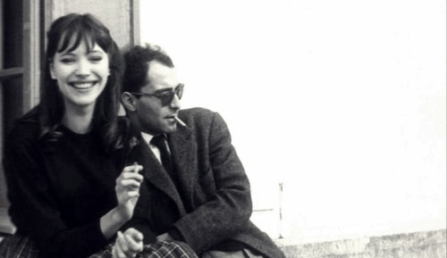 "criterioncorner:  THIS IS THE STORY OF HOW ANNA KARINA & JEAN-LUC GODARD FIRST ""GOT TOGETHER"" Anna Karina: That happened while we were shooting the picture in Geneva. It was a strange love story from the beginning. I could see Jean-Luc was looking at me all the time, and I was looking at him too, all day long.  We were like animals. One night we were at this dinner in Lausanne. My boyfriend, who was a painter, was there too. And suddenly I felt something under the table – it was Jean-Luc's hand. He gave me a piece of paper and then left to drive back to Geneva. I went into another room to see what he'd written.  It said, ""I love you.  Rendezvous at midnight at the Café de la Prez."" And then my boyfriend came into the room and demanded to see the piece of paper, and he took my arm and grabbed it and read it.  He said, ""You're not going."" And I said, ""I am."" And he said, ""But you can't do this to me.""  I said, ""But I'm in love too, so I'm going."" But he still didn't believe me. We drove back to Geneva and I started to pack my tiny suitcase.  He said, ""Tell me you're not going."" And I said, ""I've been in love with him since I saw him the second time. And I can't do anything about it."" It was like something electric. I walked there, and I remember my painter was running after me crying. I was, like, hypnotized – it never happened again to me in my life. So I get to the Cafe de la Prez, and Jean-Luc was sitting there reading a paper, but I don't think he was really reading it. I just stood there in front of him for what seemed like an hour but I guess was not more than thirty seconds. Suddenly he stopped reading and said,"" Here you are. Shall we go?"" So we went to his hotel. The next morning when I woke up he wasn't there. I got very worried. I took a shower, and then he came back about an hour later with the dress I wore in the film - the white dress with flowers. And it was my size, perfect. It was like my wedding dress. We carried on shooting the film, and, of course, my painter left. When the picture was finished, I went back to Paris with Jean-Luc, Michel Subor, who was the main actor, and Laszlo Szabo, who was also in the film, in Jean-Luc's American car. We were all wearing dark glasses and we got stopped at the border – I guess they thought we were gangsters. When we arrived in Paris, Jean-Luc dropped the other two off and said to me, ""Where are you going?""  I said, ""I have to stay with you. You're the only person I have in the world now."" And he said, ""Oh my God."" Extract taken from an interview with Anna Karina conducted by Graham Fuller in Projections 13: Women Film-makers on Film-making, edited by Isabella Weibrecht, John Boorman and Walter Donohue (Faber & Faber, 2004)  (via Focus Features)"