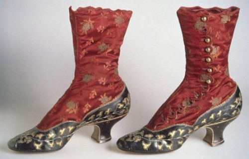 """Boots: 1883, high-button style of silk satin brocade with kidskin vamp, quarter, and baby French heel, kidskin decorated with cut-out pattern of rhododendron leaves underlaid with gold-colored kid, scallop-edge closure along side with circular brass buttons."""