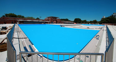 Grab Your Suit! The Pool Is Almost Open McCarren pool, opened in the summer of 1936, on the Greenpoint-Williamsburg border in Brooklyn, is now being reopened after 28 years of being closed. The pool complex, which sits in McCarren Park, has undergone a $50 million restoration, and is set to reopen ayyy the end of June. and the enormous rectangular pool has been turned into a giant U, with the placement of a concrete beach at its center. Grab your suit!