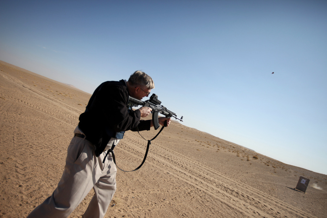 An aid worker learns how to fire a Kalashnikov rifle in the desert outside of Lashkar Gah, Helmand Province as part of an effort by security contractors to acquaint NGO staff with live fire in case of an attack during the height of the Civilian Surge. Photo: John Wendle The war in Afghanistan is not over. Help us tell the story. Fund our Kickstarter.