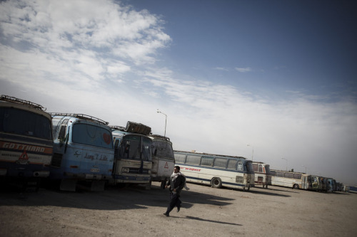 A man hurries to catch a ride at the bus station in Herat. Illegal Taliban checkpoints continue to be a security threat to Afghans traveling around the country - especially to those carrying any kind of foreign aid agency or government IDs. Photo: Sandra Calligaro The war in Afghanistan is not over. Help us tell the story. Fund our Kickstarter.