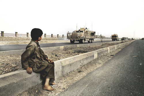 A young boy watches a NATO convoy of IED-resistant vehicles drive by on their way to the Provincial Reconstruction Team base in Lashkar Gah, the capital of Helmand Province. Photo: Jonte Wentzel The war in Afghanistan is not over. Help us tell the story. Fund our Kickstarter.
