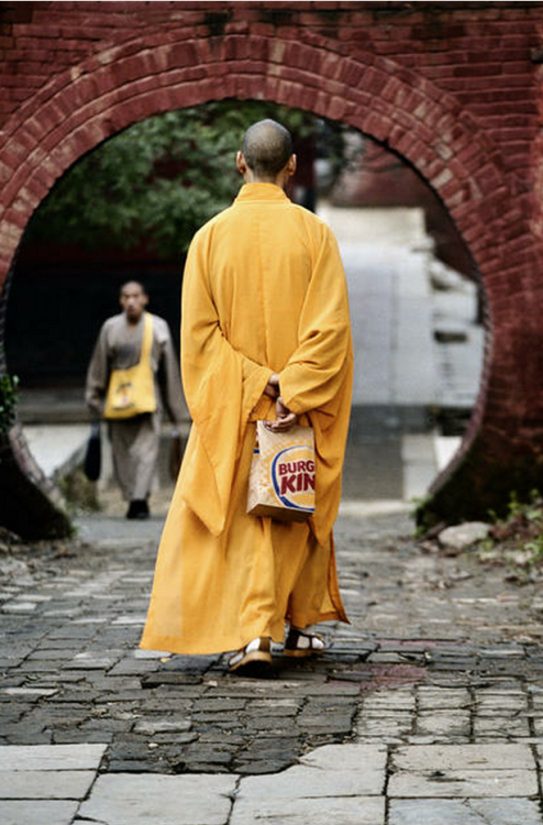 dr0gon:  A monk at the Shaolin temple in Henan Province walks with a Burger King bag.