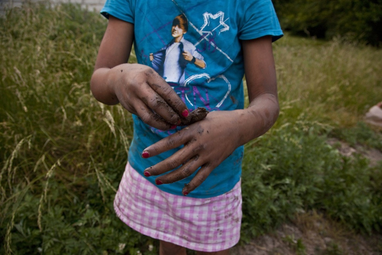 Fingernails painted, a young girl plays with mud at a community garden for Karen and Karenni refugee families who have resettled in Indianapolis, Indiana. The two Burma/Myanmar ethnic groups possess little to no English language skills upon arrival to the United States.  Most of which come after living in Thailand refugee camps with merely a primary school education, but some are able to speak two to three other languages of neighboring ethnic cultures within and near their homeland.  Photographed May 26, 2012 photo credit & copyright Gary Dwight Miller