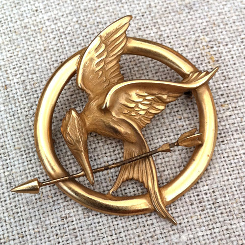 The real movie Mockingjay Pin The Pin was created by the jewelry designer Dana Schneider.  Dana gave her Hunger Games mockingjay pin a vintage look by creating it out of gold-plated sterling silver that is supposed to look old and forgotten.   She also designed jewelry for movies like Green Lantern, Terminator, X-Men, Elektra, Matrix.