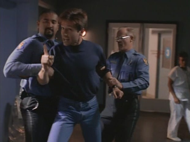 Two police officers manhandling an enraged Fox Mulder on casual Friday.