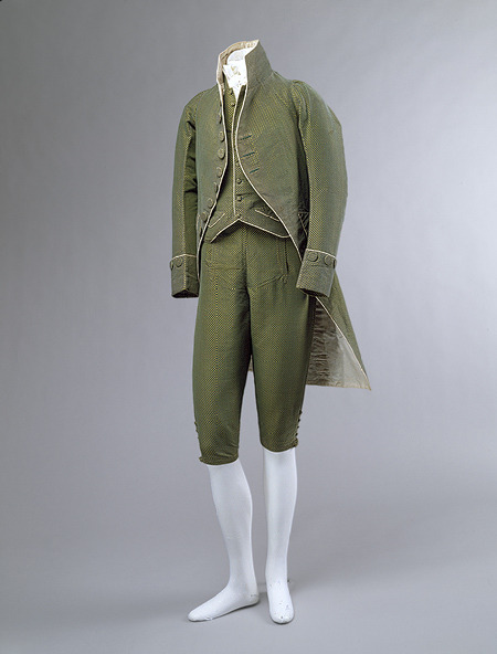 "Men's ensemble, ca. 1790FrenchThree-piece men's suit composed of tailcoat, waistcoat, and breeches of green silk velvet with green and yellow silk brocade and ivory silk twill and ivory linen lining  @credits  The dualities and contradictions that characterized male fashion in the early Napoleonic period are captured in this spectacularly schizophrenic ensemble. Under the disintegrating forces of the French Revolution (1789–94), the eighteenth-century confidence, some might say smugness, in its uniformity of aesthetic beliefs was to disappear. The restless need for social and political reform, which began in the 1780s and was fostered through the works of the philosophes, resulted in new patterns of consumption and new forms of self-expression. For a time, however, the ideas, values, and aesthetics of the ancien régime competed and coexisted with those of the founding Republic. This jockeying for position between the old and new elites gave birth to a variety of hybrid or transitional styles of dress, this suit being an outstanding example. Comprising a coat with narrow sleeves and a straight, cutaway skirt, a short vest or gilet, and a pair of breeches that covered the legs below the knees, it recalls the cool Neoclassicism of the Enlightenment. At the same time, its simple lines and complete absence of decoration reflects the Anglomania that had been a feature of male fashions in France since the 1740s, but which came to the fore in the 1780s. The opulence and frenzied frivolity of ancien régime court dress or habits à la française, however, remain in its luxurious fabric and its lurid, effervescent color. Its stand-up collar is also a vestige of the old order, but its exaggerated height anticipates the style of the Incroyables. Like these giddy young men of the mid- to late 1790s, the wearer of this suit was almost certainly an élégant, an ""enlightened"" aristocrat who hid his anti-Jacobin tendencies by adopting the puritanical design vocabulary of the republicans."