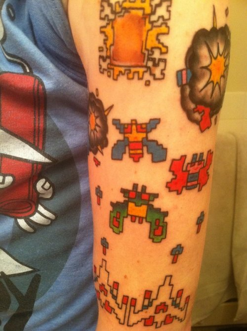 "it8bit:  Galaga vs. Grilled Cheese Pixel Tattoo Gaming and cheese fan Travis explains: ""This is my awesome Galaga arm tattoo. Not only is it retro gamey, but the pixelated grilled cheese at the top is for a local grilled cheese restaurant here in Cleveland called Melt. If you get a tattoo resembling their logo you get 25% off for life! So my tat is doubly cool"". (via: fashionablygeek)"