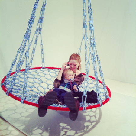 Swinging on polyethyline ropes with a baby on your lap is not exactly the weightless experience you expected from a museum trip. Participatory exhibitions are everywhere (Carsten Holler, Richard Serra, Tomás Saraceno, etc.), so don't be surprised  how touchy-feely and interactive your next museum visit can be. The Ævar is an installation made by Icelandic artist Dagbjört Ylfa Geirsdóttir and exhibited at the Reykjavik Art Museum. Hovering over thin air, in a mesh of rope and fish nets, is art student Edda with 15-month old bundle of mumbles Kormákur. (photo by Guðný Jónsdóttir)