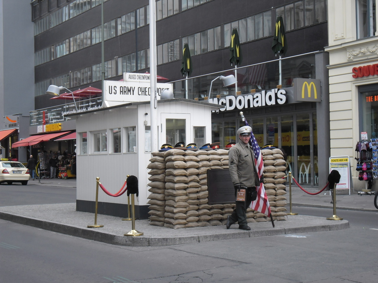 "paris-pluie:  Berlin Wall (Part I) Checkpoint Charlie in Berlin, Germany. Hopefully, you all recall the basics of the Berlin Wall from history class, but here is a recap if you'd like a refresher: After World War II, Germany was under the control of the Allies, who divided it in half. West Germany was a capitalist state and consisted of three zones under French, British, and American control respectively. East Germany was controlled by the Soviets and was a Communist state. Located deep inside East Germany was its capital city, Berlin. Like the country, Berlin was also divided in half. East Berlin was controlled wholly by the Soviets, like the rest of East Germany, but West Berlin was again divided into three zones: French, British, and American. Before the Wall, Berlin was like a hole through which people could escape to the West. The Americans were VERY eager to collect as many defectors as possible. Any East German could come to the American sector of West Berlin and request to leave the GDR (East Germany). The Americans would fly them to West Germany and set them and their families up with a job and temporary apartment. Easy. Millions of East Germans did exactly this. This caused a ""brain drain"" of Communism, with all the young, smart, and ambitious East Germans moving to the West. So, literally overnight in the early hours of 13 August 1961, the GDR officials set up a barbed-wire fence around the entire area of West Berlin. It was insecure and there were many escape attempts, so it was gradually replaced with the concrete wall we know today. Because people still needed to get into West Berlin, several checkpoints were set up where border crossings were possible. Each was run by whichever Allied power controlled the entering zone of West Berlin. The checkpoints were named by letter and referred to by the corresponding word of the NATO alphabet (Alpha, Bravo, etc). This is where the name ""Checkpoint Charlie"" comes from; it's just another way of saying ""Checkpoint C"". Checkpoint Charlie was a border crossing between the Soviet and American sectors, and it was the single East Berlin border crossing that was open to foreigners. So, any non-German wishing to enter East Berlin was obliged to enter through Checkpoint Charlie. This is why it became the most famous East-West checkpoint in Germany. Photo 1 : Sign entering the American zone from Friedrichstraße. Photo 2 : Passport check booth. Nowadays, the guy in front of it will pose with you in a photo for €5. For another €5, you can even get your passport stamped with East/West German border stamps. Photo 3 : View of Checkpoint Charlie from Friedrichstraße on the Soviet side. Note the photo of the American soldier looking out into the former Soviet zone. Photo 4 : Photo of Checkpoint Charlie from the American zone. You can see the ""last Kremlin flag"" hanging in tatters from the building. In fact, it's merely a facsimile; the real flag was taken down and is kept preserved somewhere. Photo 5 : The famous ""you are leaving the American zone"" sign. Personal anecdote: my grandfather moved to Berlin in 1990, just after the reunification of Germany. His first visit to the city was in October 1989… less than one month before the wall came down on 9 November 1989! He was among the very last people to legally pass through Checkpoint Charlie! (Photos taken by me, 13 May 2012.)"