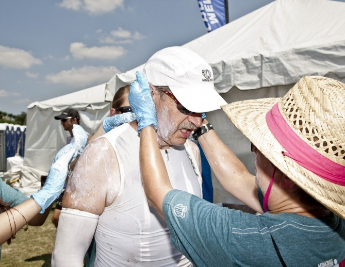 Volunteers lather my dad with sunscreen in the transition area before the marathon section of the Memorial Herman Texas Iron Man. See the rest of the project here.