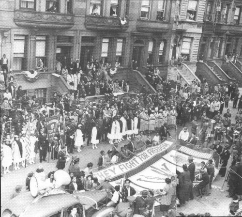 "A ""Double V"" campaign celebration in 1942 on 119th Street, between Lenox and 7th (now Malcolm X Blvd and Adam Clayton Powell Blvd) in Harlem. The Double V campaign was started in 1942, just as World War II began, by the Pittsburgh Courier, an historic African-American newspaper. ""Double V"" stood for ""Victory Abroad and Victory at Home"" and the purpose was to call continued attention to the legal injustices and segregation that Blacks dealt with as American citizens on American soil and as soldiers abroad within the (segregated) armed forces. To appreciate the role of the Pittsburgh Courier in this campaign, keep in mind that white newspapers did not cover Blacks unless there was a crime involved or, of course, if the Black in question was an athlete or an entertainer. White newspapers did not cover our births, deaths, weddings or any other slice of life-type activity that we did just like everyone else. That is why, in part, Ebony magazine was born. And they certainly did not report on racial discrimination (especially within the military where Black newspapers were banned from its libraries during the Double V Campaign) the way the Black press did."