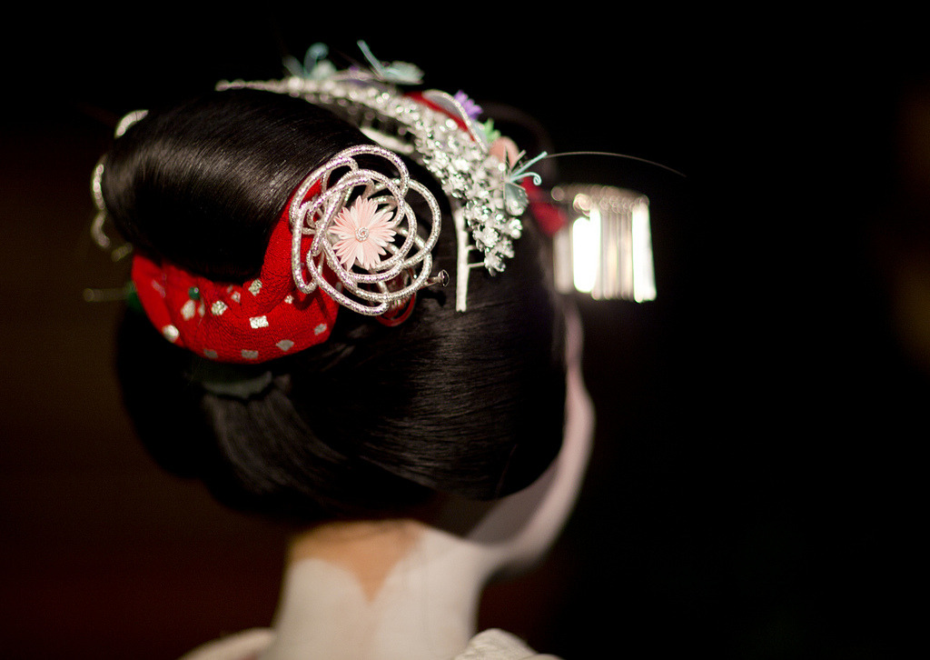 "okiya:  Katsuyama hairstyle  ""Each July for the Gion Matsuri, senior Maiko wear the Katsyuama hairstyle (also sometimes referred to as marumage despite a noticeable difference between the two styles) with special kanzashi to represent the summer. The origin of the katsuyama is directly linked back to 17th century Edo to a very popular and famous tayuu of the same name. It is also often seen in historical plays, although the actual style is slightly more exaggerated. The Katsuyama was also widely worn through out the Edo era by married women, and only went out of fashion at the beginning of the Showa era with the introduction of a new style called sokuhatsu, a style reminiscent of Charles Dana Gibson's ""Gibson Girls"". Women were encouraged to wear the shokuhatsu due to it being more conventional and hygienic, and of course, more modern. Aside from the ordinary hana-kanzashi and jade tama-kanzashi, Maiko wear a special pink and silver circular kanzashi called bonten that sits in the middle of the mage showing through on both sides. A thick red ribbon made from ro silk with various patterns in silver/gold is also woven around the base and through the centre of the mage."" (source: ImmortalGeisha)"