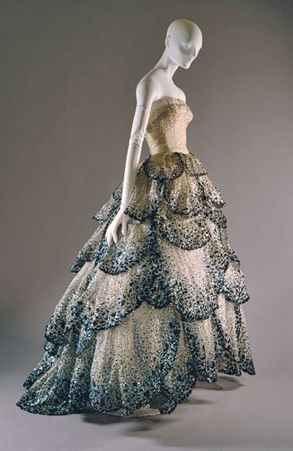 What Would Khaleesi Wear? Wedding Edition Christian Dior dress, 1950. The blue, black, and silver rhinestones against the beige dress is exquisite and can both be the something-blue and for her, Dothraki ceremonial blue; the pattern of scale-like petals gradually increasing in size to the bottom; the detailed sequins throughout the gown as well as on the bodice: brilliant.