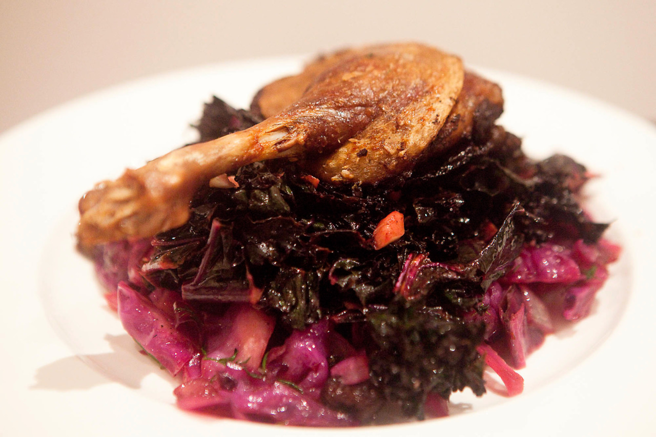 "Crispy Orange Duck Leg with Sauteed Kale, Red Cabbage and Raisins I absolutely love duck.  It's really got to be my favorite meat, if only it wasn't so bloody expensive.  Every now and then I'll see it at an ok price and treat myself; this was a delicious meal and the standout was this recipe I found for the red cabbage and raisins.  I had some mixed dried fruit I used instead, but it was a great side for this dish and there was enough leftover that I had it with pork belly the next night (recipe, coming up!). Kale was just sauteed with some garlic and lemon.  The duck was lacking a bit of liquid so I've altered the recipe slightly to ""what I would have done"". Ingredients (crispy orange duck leg): 2 duck marylands 1 tbsp Chinese Five Spice 1 orange, quartered 1 tsp cinnamon 1 red onion, sliced 1/2 cup of orange juice 1/2 cup verjuice or white wine Salt, pepper, and olive oil Pat the top of the duck leg dry, and season the underside with the five spice, cinnamon, salt and pepper.  Salt the top of the duck skin, and in a hot oven proof pan with a bit of olive oil, sear the duck skin for about 5 minutes until brown. Remove the duck and saute the onion until soft.  Squeeze in the juice from the orange quarters and throw the rinds into the pan.  Add the juices, season with salt and pepper, and place the duck legs in meat side down.  Roast in the oven for about 40 minutes at 170C / 325F.  10 minutes before the end of cooking, baste with the pan juices, and make sure the skin is super crispy (you may need to turn your oven, or the grill, up)."