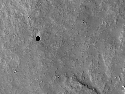 A Hole in Mars  Credit: NASA, JPL, U. Arizona  Back in 2007, black spots were discovered on Mars that are so dark that nothing inside can be seen. Quite possibly, the spots are entrances to deep underground caves capable of protecting Martian life, were it to exist.  The unusual hole pictured above was found on the slopes of the giant Martian volcano Arsia Mons. The above image was captured three weeks ago by the HiRISE instrument onboard the Mars Reconnaissance Orbiter currently circling Mars.  The holes were originally identified on lower resolution images from the Mars Odyssey spacecraft, The above hole is about the size of a football field and is so deep that it is completely unilluminated by the Sun. Such holes and underground caves might be prime targets for future spacecraft, robots, and even the next generation of human interplanetary explorers.