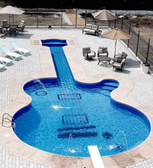 designed-for-life:  This amazing swimming pool shaped like a guitar proved to be a challenge for its designers and builders – Canadian Aqua-Tech Company. Their client, a passionate guitar collector who walked in their office looking for a hot tub, had a sudden change of heart and approached them with an odd, yet interesting idea. Wanting a guitar-shaped swimming pool in his backyard, the client was presented with an exact replica of a Les Paul Custom guitar – shaped in fine details and exemplary displaying creativity in design and construction. Measuring 19 meters long, the inspiring swimming pool is unique – imagine how the owner and his wife feel every time they dive in. Blue water makes the vinyl-lined pool dance with each movement and create a blurred, dynamic effect. Equipped with two sets of stairs, the undulating design proves to be a bold and creative addition to a guitar collector's backyard.