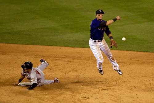 DENVER, CO - MAY 28: Troy Tulowitzki #2 of the Colorado Rockies makes an acrobatic throw to first base to complete the double play to end the 10th inning as Marwin Gonzalez #9 of the Houston Astros slides into second during the 10th inning at Coors Field on May 28, 2012 in Denver, Colorado. The Rockies defeated the Astros 7-6 in 10 innings/ (Photo by Justin Edmonds/Getty Images)