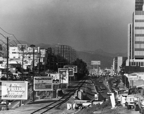 Circa 1970s view, looking east, of Santa Monica Boulevard near Century City. The abandoned tracks of the Pacific Electric Railway run down the middle of the photo.