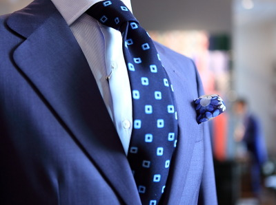 "Suit, tie, and ps in several shades of blue"", with a rounded gorge / Traje, corbata y pañuelo en distintos tonos de azul"", con solapa redondeada"