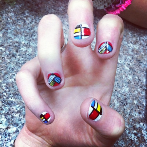 Mondrian manicure by Ria Nailz with feather accent nails. Nail art hand painted over single color solid coat.
