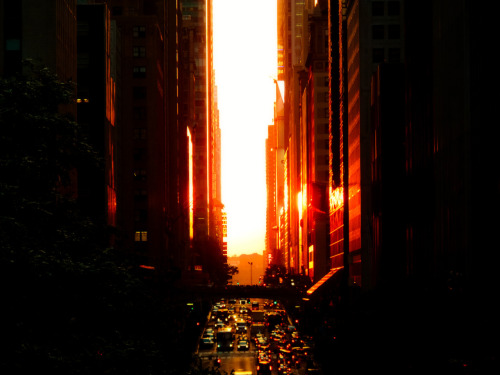 "Manhattanhenge Sunset Overlooking 42nd Street and Times Square. New York City  There is nothing quite like the intensity of seeing the sun spread it's light like wildfire through the streets of midtown Manhattan. The red light glows with the ferocity of a supernova showering its splendor onto the urban landscape.  In honor of tonight's Manhattanhenge sunset which may or may not be hidden by storm clouds since New York City's weather has been highly unpredictable and stormy as of late, this is a photo I took exactly a year ago during last year's Manhattanhenge. The buildings in this photo are the buildings in Times Square (you can make out the Madame Tussauds sign).  Manhattanhenge is a semiannual occurrence in which the setting sun aligns with the east–west streets of the main street grid in the borough of Manhattan in New York City. The term is derived from Stonehenge, at which the sun aligns with the stones on the solstices. It was coined in 2002 by Neil deGrasse Tyson, an astrophysicist who is the director of the Hayden Planetarium at the American Museum of Natural History.   —-  I was really overwhelmed by the response to my post yesterday about the difficulties of monetizing photography (or anything) online.  I posted it, thought about deleting it more than a dozen times, walked away for a few hours last night to get some things done and came back to a flood of responses. I am mostly floored by the experiences shared with me that are so similar in scope to what I have been through. You can view the nearly 200 comments and interesting ensuing discussion over at the post on Google Plus if you wish.  I will reply to all the comments and emails today and tomorrow when I have the time. I wrote the post because I saw a lack of discourse on the painful realities of social media and online marketing. I didn't realize how much it would resonate with people. Thank you so much to all who weighed in on the discussion.   —-  View this photo larger and on black on my Google Plus page —-  Buy ""Manhattanhenge Sunset Overlooking 42nd Street and Times Square - New York City"" Prints here, email me, or ask for help."