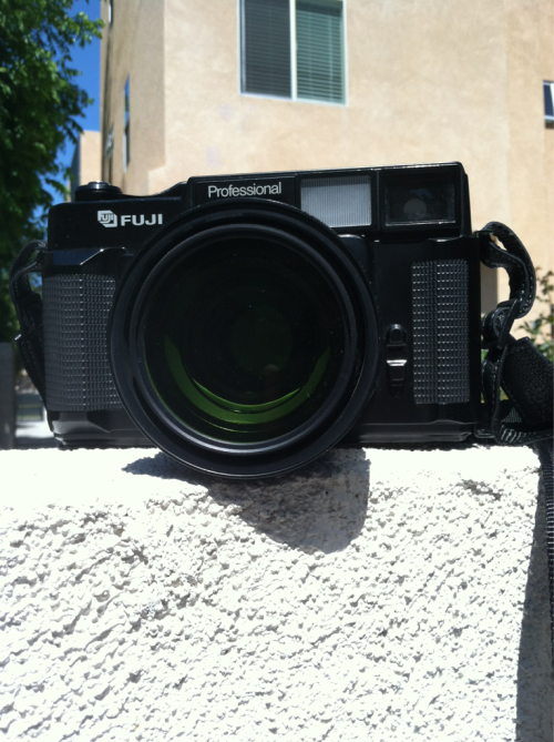 Fuji GW690  f=90mm F3.5. During its last CLA, the name ring had to be broken up to take the camera apart. Takes a 67mm filter and currently has a yellow-green filter attached. No cracks or dents on the body.