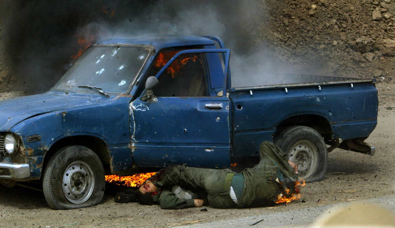 A burning Iraqi officer tries to escape an ambush while clambering over the body of his dead comrade.