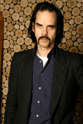 Nick Cave is cross. He's wearing his 'fun socks' but his pants are too long for people to appreciate them properly.