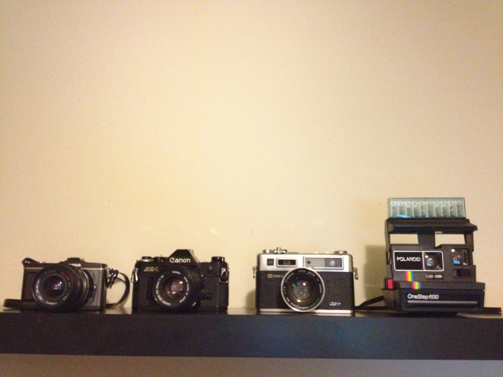 Right to left: Olympus Pen e-p2, Canon AE-1, Yashica electro 35, polaroid onstep 600  Camera Porn :-)