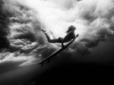 Surfer duck diving under a wave.  Follow our blog. New travel photography & videos posted daily.