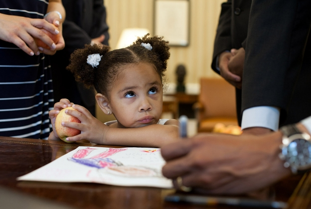 "Luz Graham-Urquilla, 4, watches President Barack Obama as he signs her drawing. ""Hey! Sign your own darn drawing. I worked hard on that."""