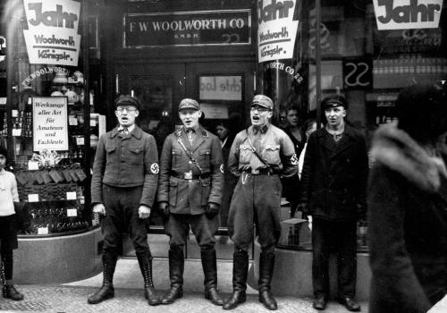 Nazi troops sing in front of a Woolworth Co. store during a movement to boycott Jewish presence in Germany, March, 1933
