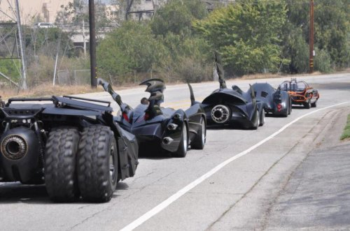 collegehumor:  Five Generations of Batmobile Driving on the Road They're all honking at the oldest Batmobile in the front.