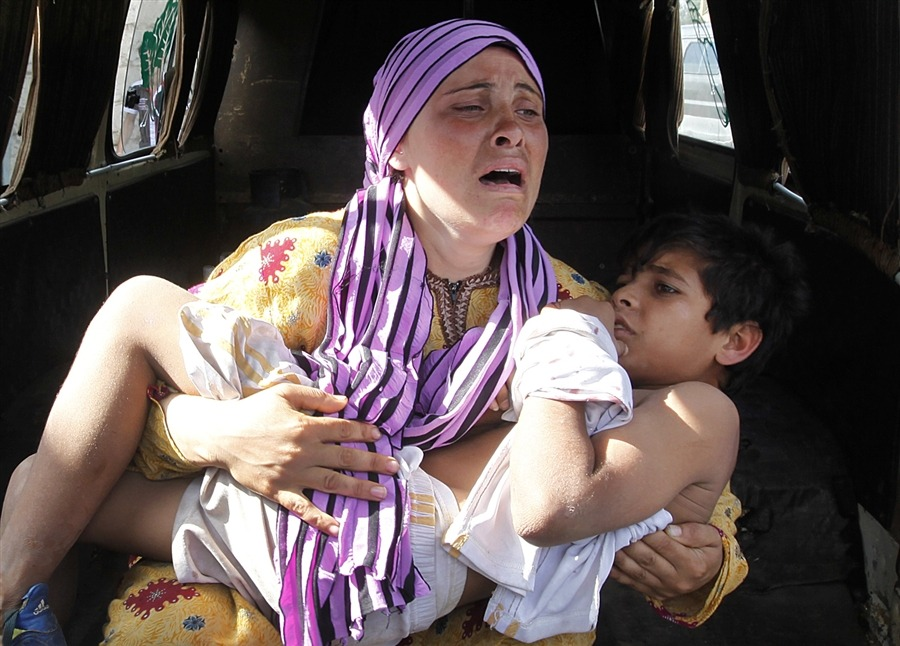 A Syrian woman, cries as she carries her injured son who was shot in his hand by the Syrian border guard when they were crossing a river from Syria to Lebanon, at the northern Lebanese-Syrian border town of Wadi Khaled,  in Akkar, north Lebanon, Wednesday, May 30. U.N. observers have discovered 13 bound corpses in eastern Syria, many of them apparently shot execution-style, the monitoring mission said Wednesday. The announcement comes days after a massacre in Houla, in the central Homs province, which killed more than 100 people and prompted worldwide condemnation against the regime of President Bashar Assad. [Credit : Hussein Malla / AP]