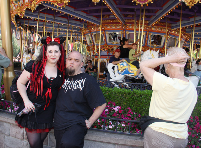 "GOTH DAY AT DISNEYLAND Last weekend, I went to the 12th annual ""Bats Day in the Fun Park."" Though you would never guess it from the name, it's a day where hundreds of goths head to Disneyland California for a day of image-subverting fun. (Seriously, who the fuck decided to call it that? What does that mean?)  The main event of the day is a group photo taken outside Cinderella's castle. This is everyone hustling into position for it. The guy in the purple didn't look like he was giving up his spot for anybody.  And this is the photo being taken. Say an edgy alternative to ""cheeeeese!""—like ""bloooooody!"", or maybe ""I always identified with Ursula more than Arieeeeeel!"" I couldn't get far back enough to get a shot of everyone, but this should give you an idea of how many people were there. I'd estimate the number of goths present to be: a shitload.  These aren't sold on-site, you have to order them online, so here's a thing I've learned: Goths are very organized.   This girl can have no idea what is going on. Do you think she looks at Donald and Micky and thinks they've just dressed up for Disneyland as well? Continue"
