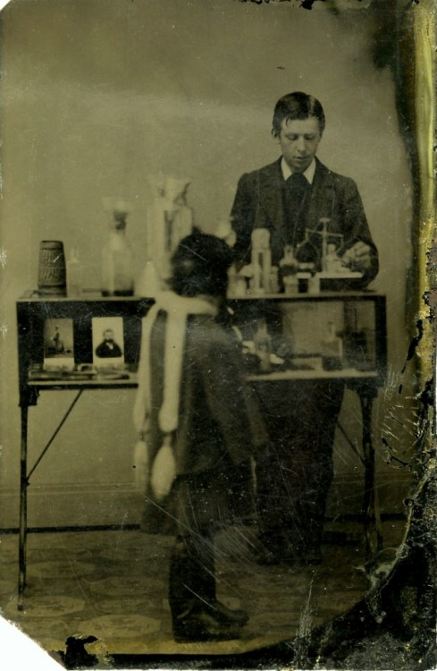 ca. 1860-90, [tintype portrait of of either a young photographer, pharmacist, or chemist with a scale, various bottles and chemicals. Another person in the foreground is turned away from the camera, admiring photos displayed in the case] via Jeffrey Kraus Antique Photographica, Tintype Collection