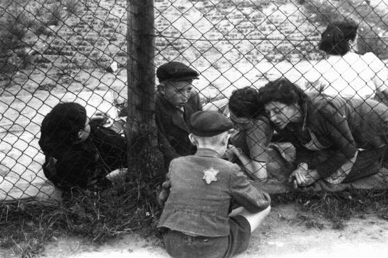 "Family members say goodbye to a child through a fence at the Lodz ghetto's central prison where children, the sick, and the elderly were held before deportation to Chelmno during the ""Gehsperre"" action. Lodz, Poland, September 1942. (via ushmm) See more at this tumblr - the-holocaust"