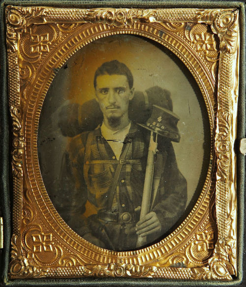 "ca. 1860's, [ambrotype portrait of a Confederate soldier wearing a plaid shirt and a holstered pistol. He carries a large bedroll, a percussion rifle and a kepi with the letters ""4 SLG"" for the 4th Sumter Light Guards] via Heritage Auctions"