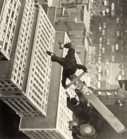 arreter:  Man balancing on a piece of wood on the roof of a skyscraper 1939.