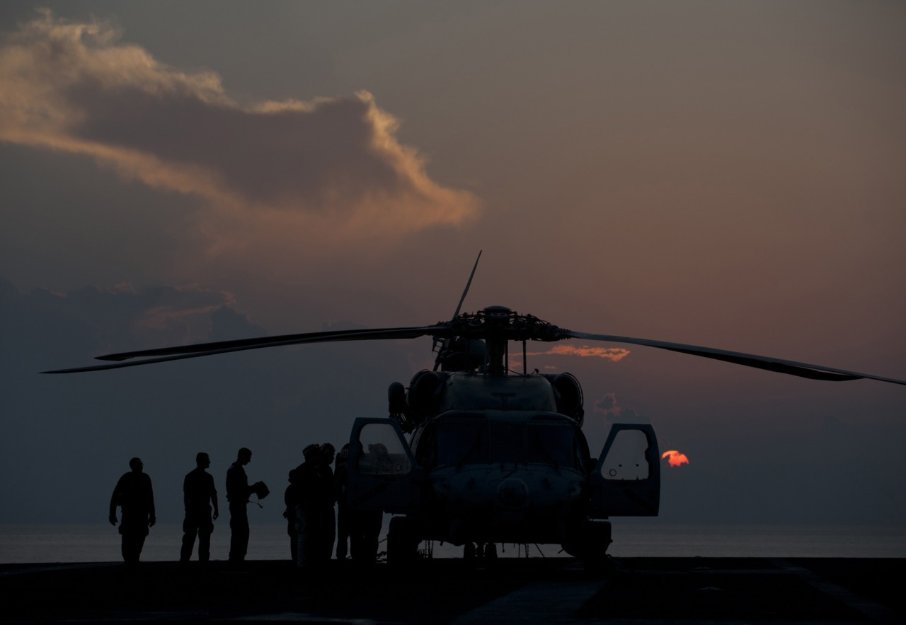 Sailors finish maintenance on a helicopter as the sun sets.