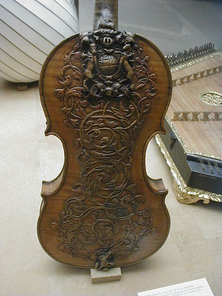 "classicalliterature:  Detailed carving on the back of a violin, seen at the Victoria and Albert Museum in London. The paper in the foreground says : ""Violin, English about 1680. Pine top and sides, sycamore back, decorated with spiral scroll work and the royal arms of the Stuarts. The final is in the form of a woman's head. The instrument is not signed but a number of names have been suggested, the most likely being Thomas Urquhart, who worked at London Bridge between 1648 and 1680. The baroque style of decoration and Royal Stuart arms would indicate that the instrument was part of the household of Charles II or James II. Charles II is known to have preferred the brisk and arie sounds of the violin to the contrapuntal fancies of the viol."""