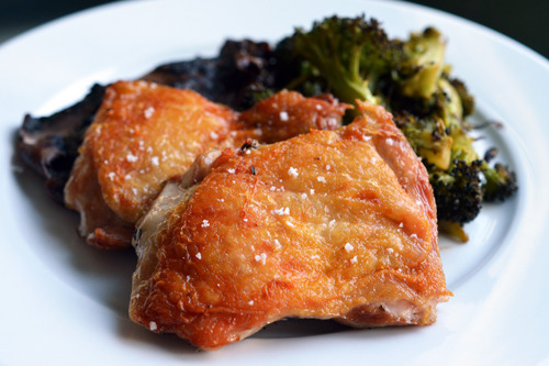 A dinner plate of paleo and Whole30 sous vide crispy chicken thighs with roasted broccoli.