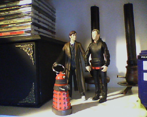 emoeba:  Yes my Dalek is crippled, I need to mix some epoxy and fix him, ok?   I made some polymer clay cake slices (with strawberries on top!) this evening.  They should be in scale with my Doctor and Master action figures.  Soon my babies can feed each other cake~ For now they're holding hands and walking a Dalek in my bookshelf.