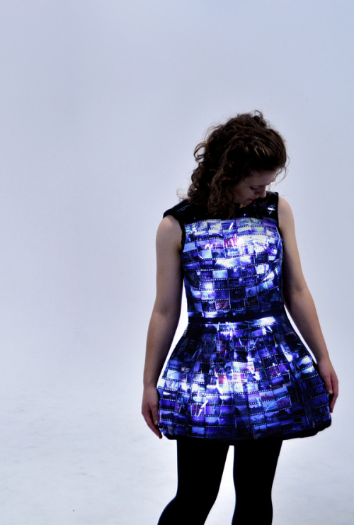 """The dress is constructed out of individual slide film images that are backed with LED's. An Arduino Lilypad connected to a light sensor controls the brightness of the LED's. The sensor reads how much ambient light there is and uses this value to determine if the LED's will be off or on. When there is lots of light the LED's are off and it looks like a shiny black dress with small hints that something else is going on. Once the sensor determines there is the right amount of light for LED's to be seen in their full brightness it turns them on. When the dress is on the lights slowly pulse and the images on the dress come alive."""