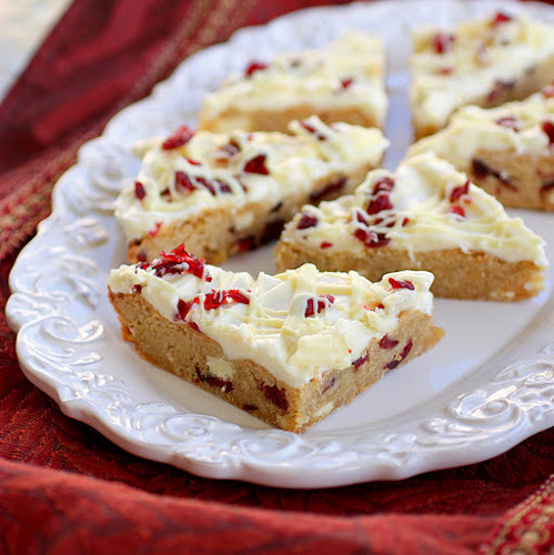 Cranberry Bliss Bars Ingredients For blondie layer: 3/4 cup (1 1/2 sticks) salted butter, cubed 1 1/2 cup packed light brown sugar 2 large eggs 3/4 tsp vanilla extract 2 1/4 cup flour 1 1/2 tsp baking powder 1/4 tsp salt 1/8 tsp cinnamon 1/2 cup dried cranberries 6 oz white chocolate (coarsely chopped) For frosting: 1 package (8 oz) cream cheese, softened 1 cup powdered sugar 6 oz white chocolate, melted 1/2 cup dried cranberries (coarsely chopped) (Optional) 1 tsp grated orange zest Instructions Preheat oven to 350 degrees. Spray 9x13 baking dish or line with parchment paper. To prepare blondie layer: In a medium bowl, melt butter for 1 minute. Stir in brown sugar. Pour into large bowl and let cool to room temperature.  Beat in eggs and vanilla with electric mixer. In a separate bowl, whisk together flour, baking powder, salt and cinnamon. Gradually add dry mixture to butter mixture. Stir in cranberries and chopped chocolate. Spread batter into prepared pan. Bake for 18-21 minutes, until a tester comes out clean. Let cool completely. To prepare frosting: Beat cream cheese and powdered sugar in a large bowl until combined. Gradually add half of the melted white chocolate and beat until blended. Frost blondies. Sprinkle with chopped cranberries. Drizzle remaining white chocolate. Let frosting set, then cut into bars. Store in refrigerator until ready to serve. —